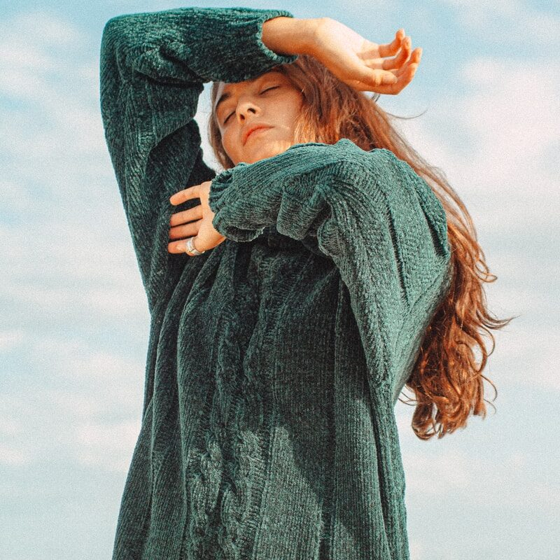 woman in blue sweater covering her face with her hand