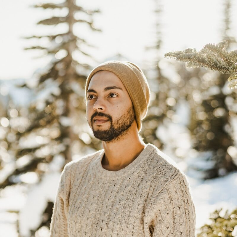 man in gray knit sweater and brown knit cap