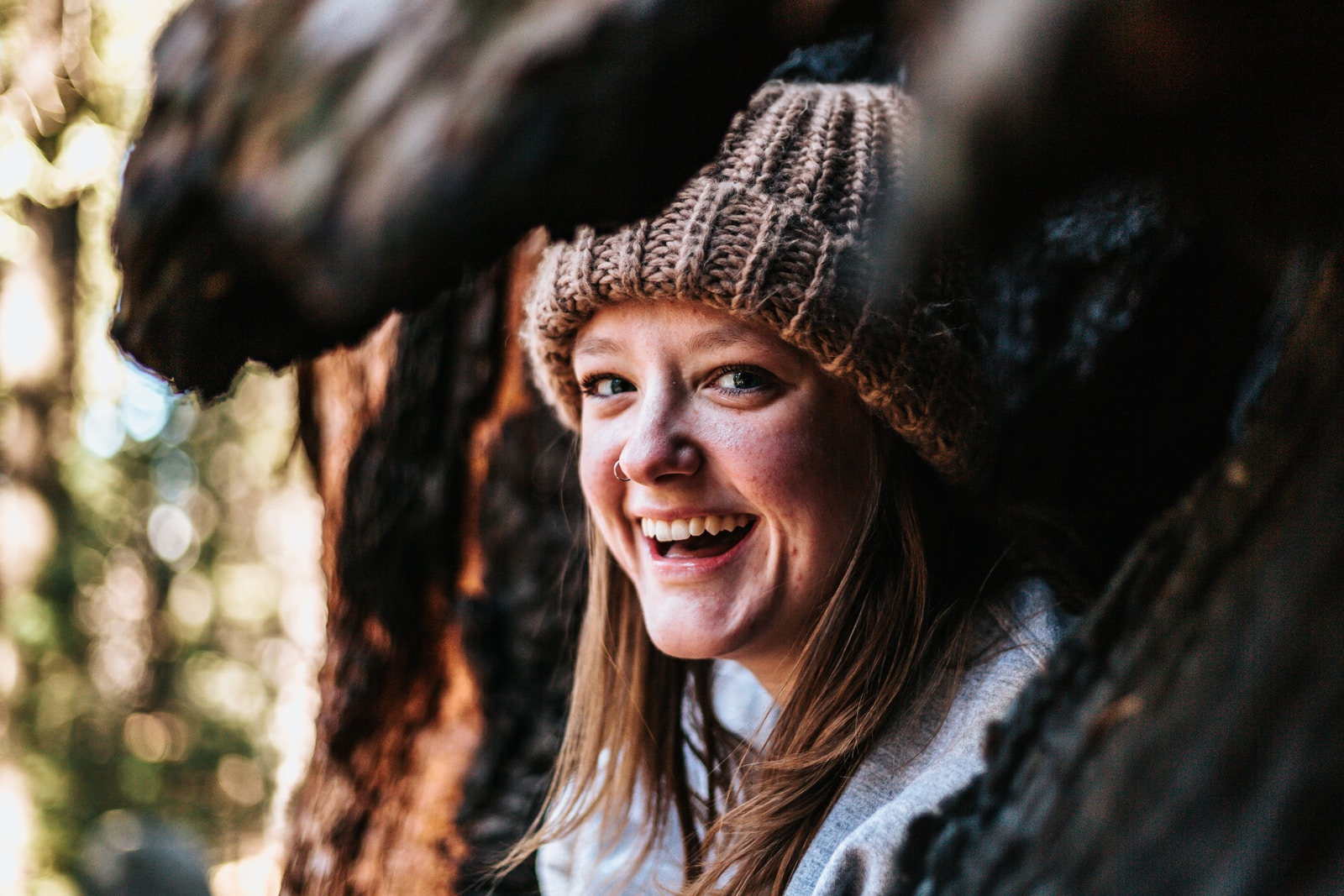 closeup photography of smiling woman beside brown tree
